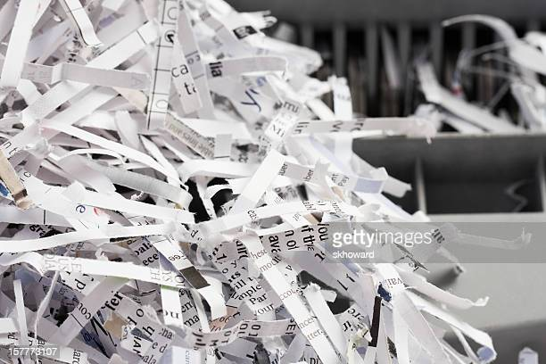 pile of shredded paper with shredder in background - shredded stock pictures, royalty-free photos & images