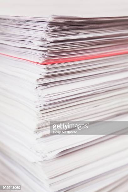 Pile of stacked white paper reports with red one sticking out
