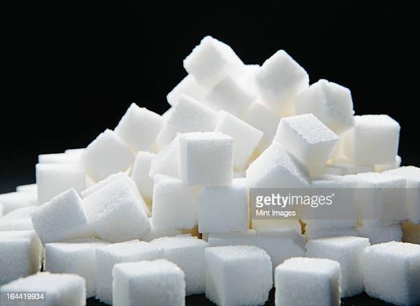 Pile of sugar cubes against a black backdrop.