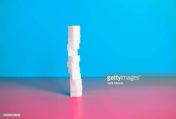 pile of sugar cubes with blue background and red background - zucker stock-fotos und bilder