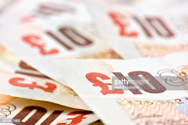 pile of ten pound british sterling notes - ten pound note stock photos and pictures