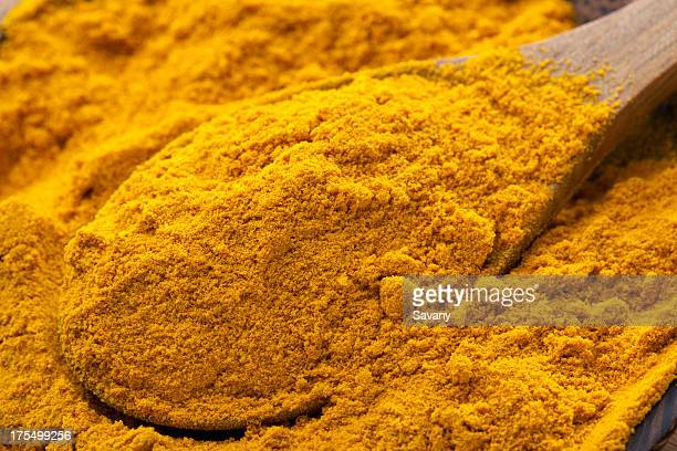 A pile of turmeric in a bowl with a wooden spoon
