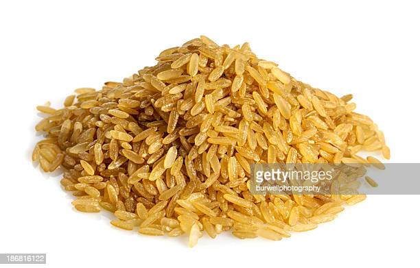 A pile of uncooked brown rice on a white background