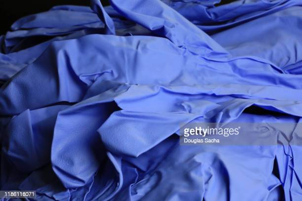 pile of unused latex surgical gloves - surgical glove stock pictures, royalty-free photos & images