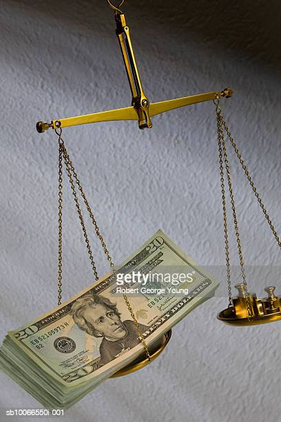 Pile of US currency on brass scales, studio shot, elevated view