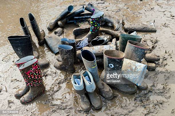 Pile of used wellington boots sit in the mud at the Glastonbury Festival at Worthy Farm, Pilton on June 22, 2016 in Glastonbury, England. Now its...