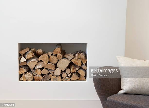 Pile of wood beside chair indoors