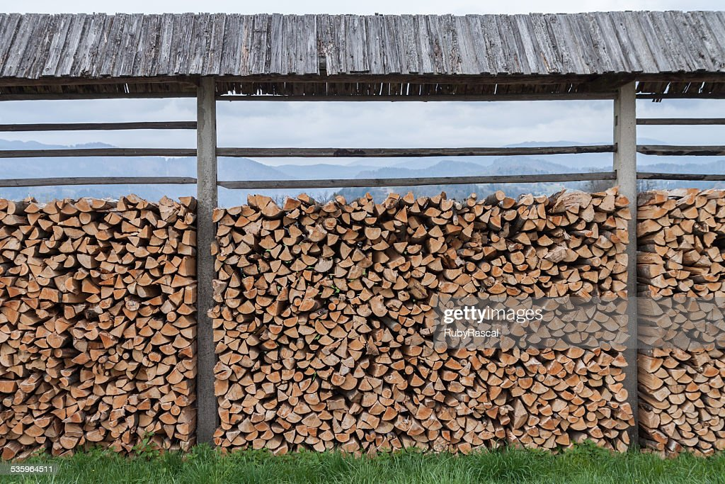 Pile of wood stacked outdoors under a shelter in Slovenia : Stock Photo