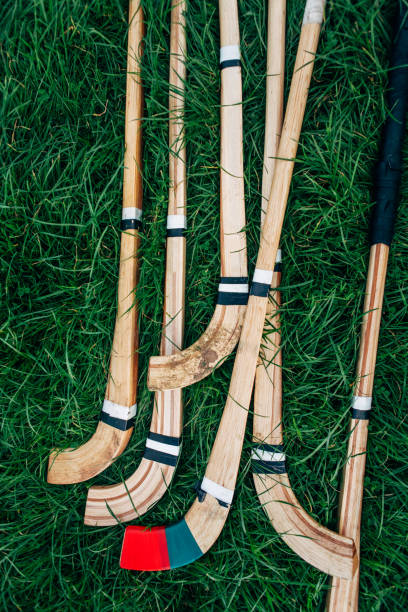Pile of wooden Shinty sticks on grass.