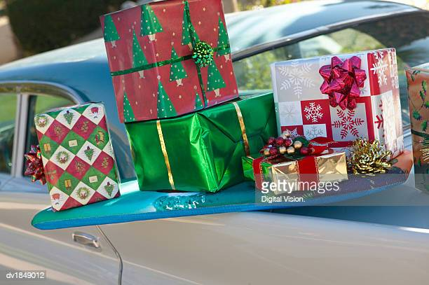 Pile of Wrapped Christmas Presents Balancing on the Back of a Classic Car