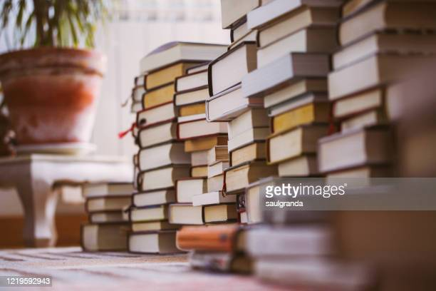 piles of books stacked on a carpet - boek stockfoto's en -beelden
