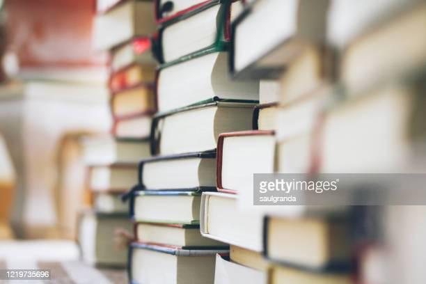 piles of books stacked on a carpet - litteratur bildbanksfoton och bilder
