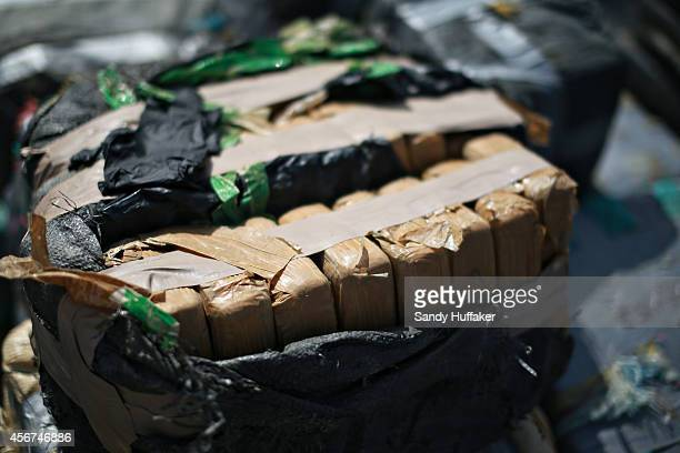 Piles of confiscated cocaine, seized during a 18 different interdictions off the coast of Central and South America, is prepared to be offloaded from...