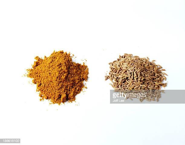 Piles of cumin powder and cumin seeds