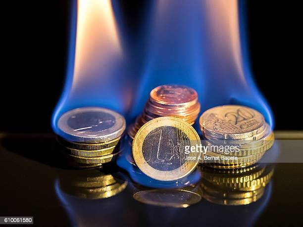 piles of euro coins in flames on a black background. Concept of crisis of the European currency