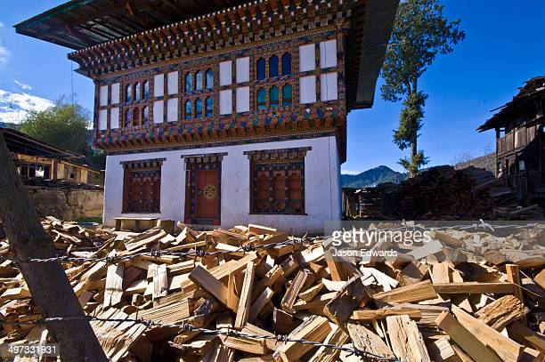 Piles of freshly cut fire wood waiting to be stacked around a Bhutanese home in preparation for winter.