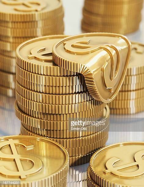 Piles of gold dollar coins, one melting