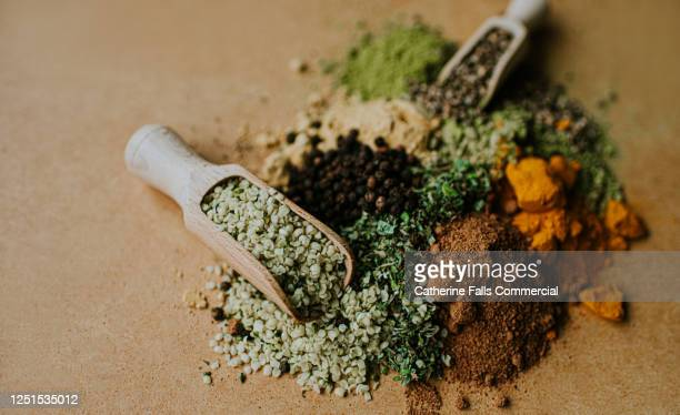 piles of herbs, spices and seasonings on a wooden surface, with scoops - refreshment stock pictures, royalty-free photos & images
