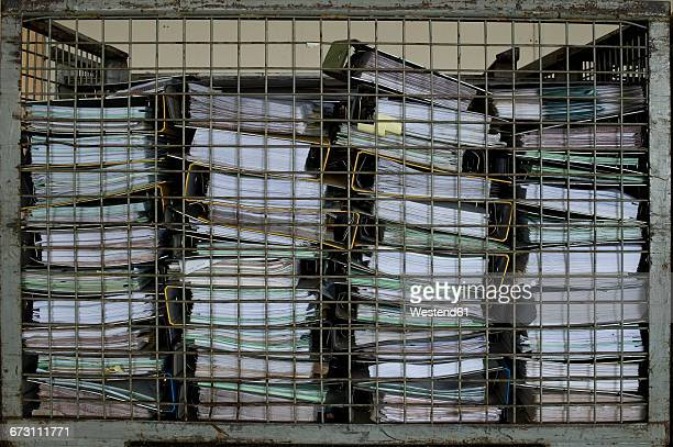 Piles of office files behind grid