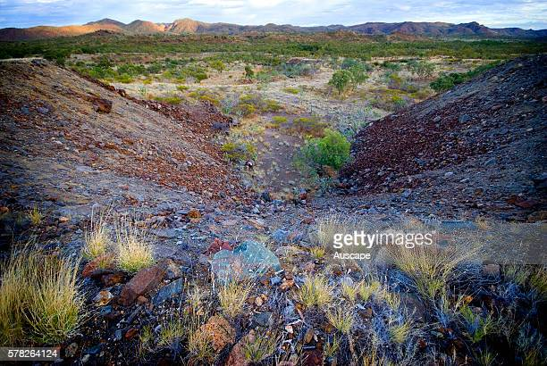 Piles of overburden at abandoned Mary Kathleen uranium mine closed in 1982 The land has been rehabilitated Selwyn Range between Mount Isa and...