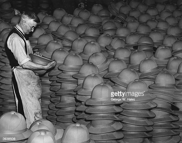 Piles of pith helmets receiving final inspection before being despatched to British troops overseas