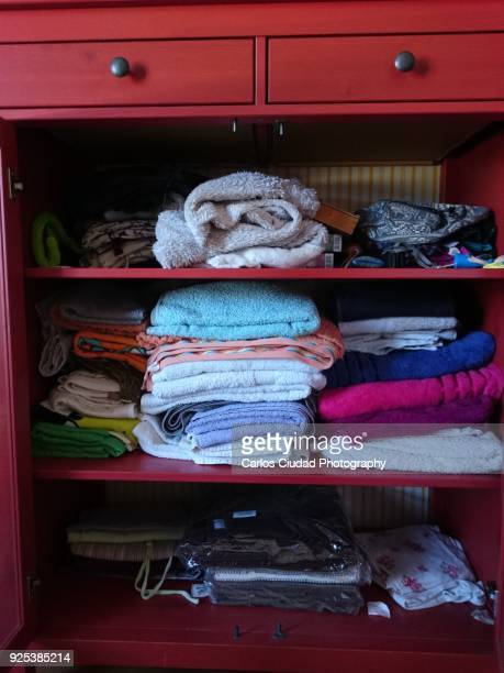 Piles of towels and other objects inside red dresser