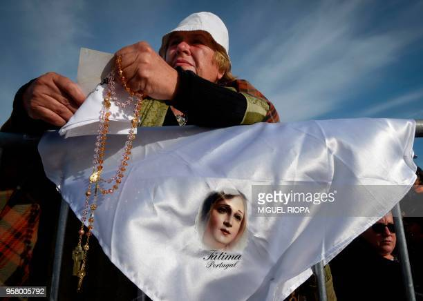 A pilgrim attends a mass ceremony at the Fatima shrine in central Portugal on May 13 2018 Thousands of pilgrims converged on the Fatima Sanctuary to...