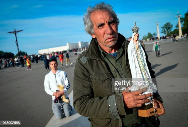 TOPSHOT A pilgrim carries a statue of Our Lady of Fatima as he arrives to the shrine of Fatima on May 13 2018 Thousands of pilgrims converged on the...