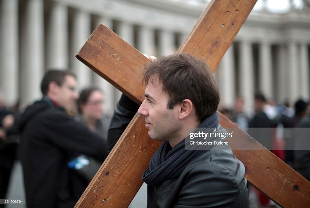 A pilgrim carries a wooden cross after taking part in a stations of the cross ceremony in St Peter's Square on March 29, 2013 in Vatican City, Vatican.