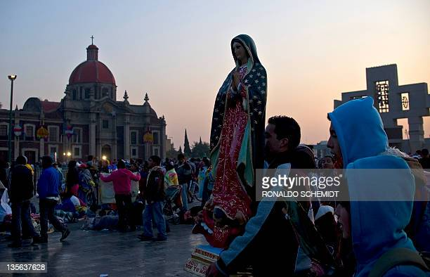 A pilgrim carries an effigy of Our Lady of Guadalupe Mexico's patron saint during annual celebrations at the Basilica of Guadalupe in Mexico City on...