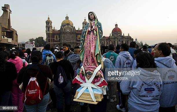 A pilgrim carries on his back a holy image at the Basilica of the Virgin of Guadalupe Mexico's Patron Saint during the annual celebrations on...