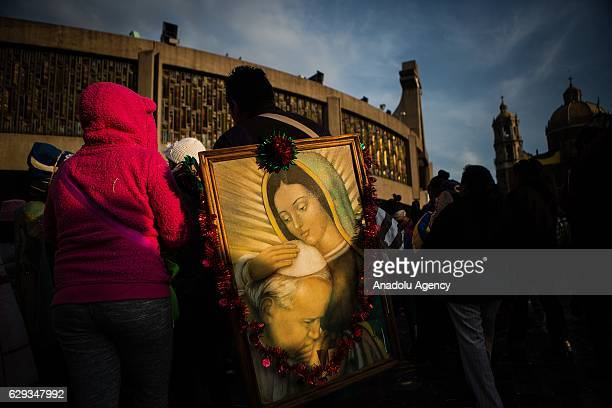 A pilgrim carrying a paint of the Virgin of Guadalupe and Pope St John Paul II is seen during the pilgrimade to the Basilica of Guadalupe in the Day...
