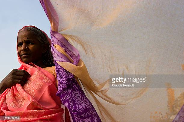 Pilgrim drying her sari after having taken her Holy bath, on the banks of the Sacred Ganges.