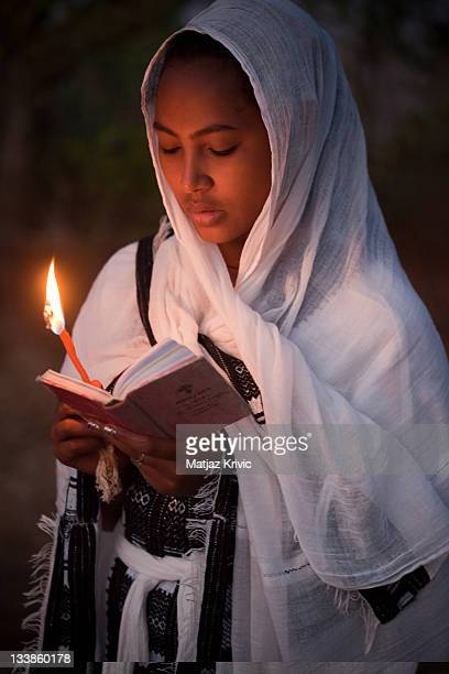 A pilgrim girl dressed in white as an Earth Bound Angel reading Holy Bible in Amharic through the night just to be near the Tabot during a Timkat...