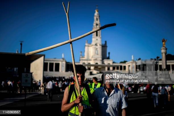 Pilgrim holds a giant crucifix at the Fatima shrine in Fatima, central Portugal, on May 12, 2019. - Thousands of pilgrims converged on the Fatima...