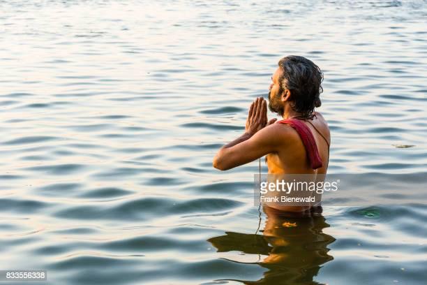 Pilgrim is praying in the holy river Ganges at Dashashwamedh Ghat, Main Ghat, in the suburb Godowlia.