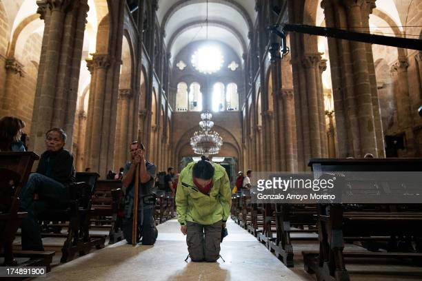 A pilgrim kneels inside Santiago de Compostela Cathedral where a memorial mass will be held for the victims of a train crash July 29 2013 in Santiago...