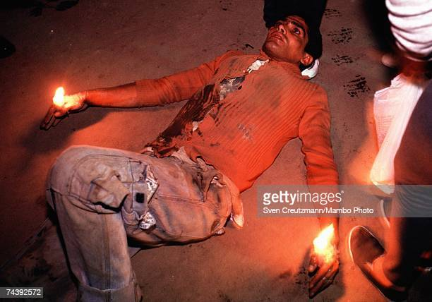 A pilgrim lays on the ground holding candles during the centuriesold annual pilgrimage to the Iglesia De San Lazaro on the Day Of Saint Lazarus on...