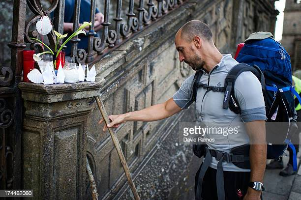 A pilgrim leaves his cane next to candles in memory of the train crash victims at the Cathedral of Santiago on July 26 2013 in Santiago de Compostela...