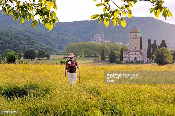 Pilgrim on the on the Way of St James arriving at the Romanesque Saint Just de Valcabrere Basilica listed UNESCO World Heritage SIte and...