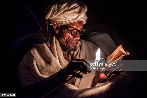 A pilgrim praying with candle lit at night outside the Biete Medhane Alem During the first days of January thousands of Ethiopian Orthodox Christian...