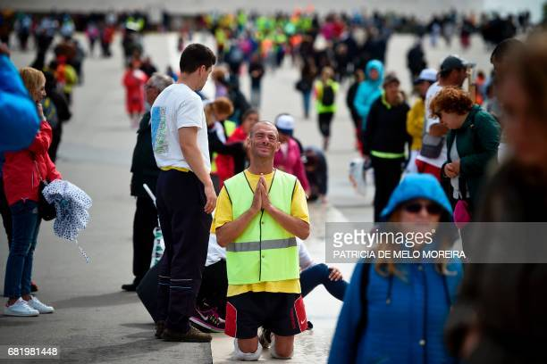 A pilgrim prays as he walks on his knees at Fatima Sanctuary in Fatima central Portugal on May 11 2017 Two of the three child shepherds who reported...