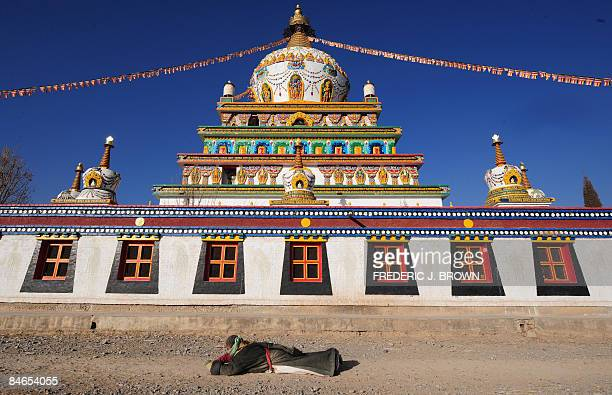A pilgrim prostrates herself in prayer while circling the fivetiered stupa at Gomar Gompa in Repkong during ongoing celebrations for Monlam or the...