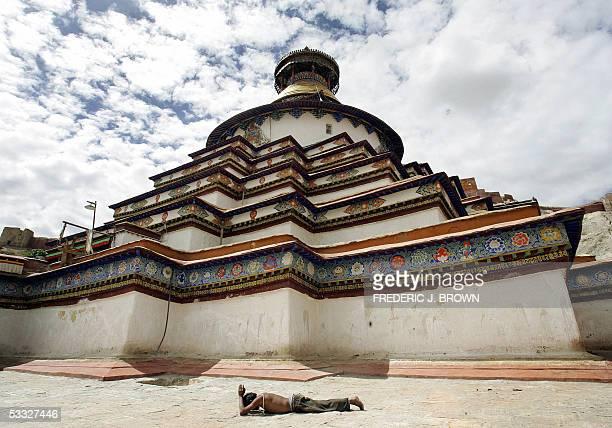 A pilgrim prostrates himself on the ground in prayer on a pilgrim circuit or Kora around the Kumbum Chorten Stupa 05 August 2005 at the Pelkhor Chode...
