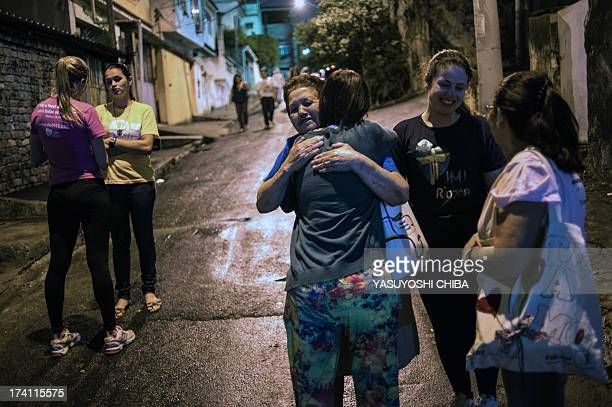 Pilgrim Rittha Ygnez Canedo Petersen da Costa greets another Catholic woman at the Alemao shantytown complex ahead of the World Youth Day in Rio de...