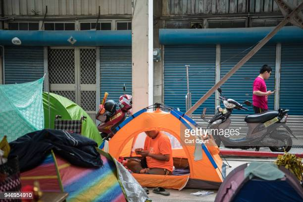 A pilgrim sits in his tent pitched near Xingang Fengtian Temple as festivities take place to mark the arrival of the statue of Mazu where it will...
