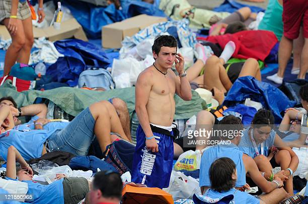 A pilgrim stands amid some of hundreds of thousands of young pilgrims who gathered in blistering heat on a vast dusty esplanade outside Madrid to...