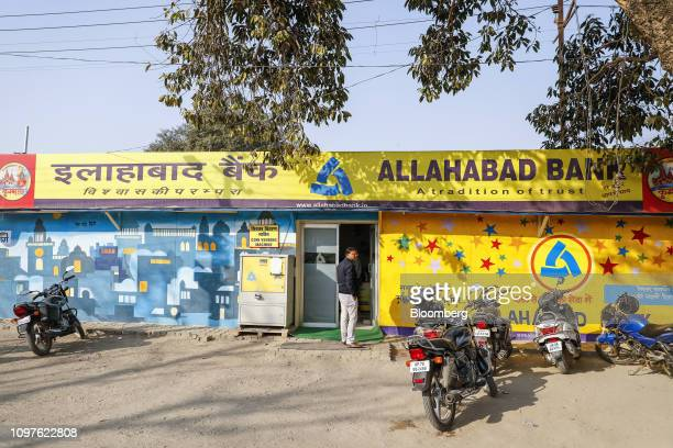 Pilgrim stands at the entrance to a temporary Allahabad Bank Ltd. Automated teller machine facility during the Kumbh Mela in Prayagraj, Uttar...