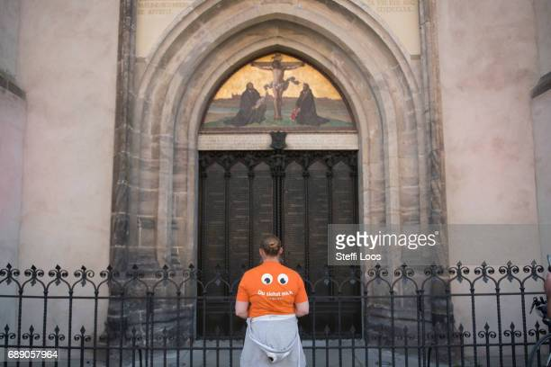 A pilgrim stands in front of the All Saints' Church the site where the Ninetyfive Theses were likely posted by reformer Martin Luther on May 27 2017...