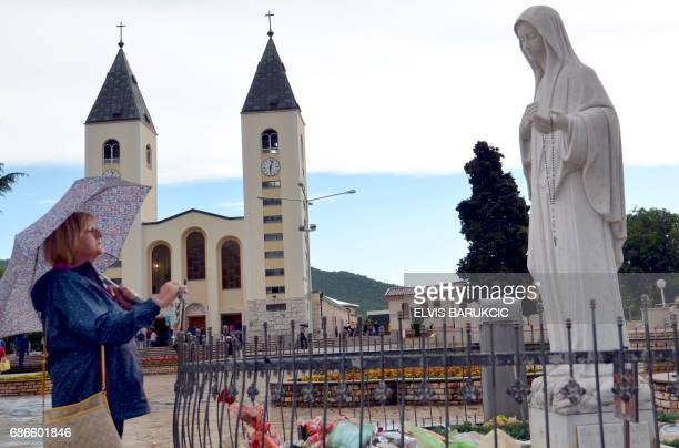 A pilgrim stands near a statue of the Holy Mother Mary on May 15 2017 in southern Bosnian town of Medjugorje Pope Francis on May 13 2017 expressed...